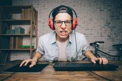 Junger Mann, der zu Hause Spiel spielt und playthrough oder Durchlaufvideo strömt Lizenzfreies Stockbild