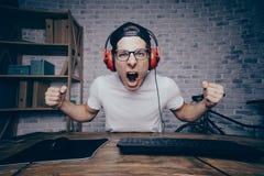 Junger Mann, der zu Hause Spiel spielt und playthrough oder Weg strömt Stockfotos