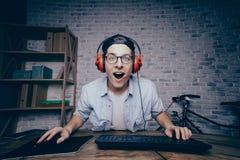Junger Mann, der zu Hause Spiel spielt und playthrough oder Weg strömt Stockbild