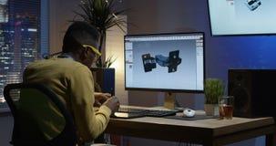 Junger Mann, der zurück siiting und ein Bild auf seinem Computer redigiert worden sein würden stock video