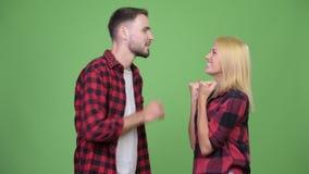 Junger Mann, der zur jungen Frau flüstert und aufgeregt schaut stock footage