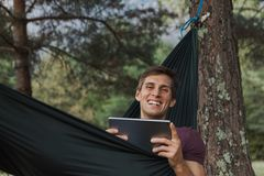 Junger Mann, der zur Kamera lächelt und eine Tablette auf einer Hängematte verwendet stockfoto
