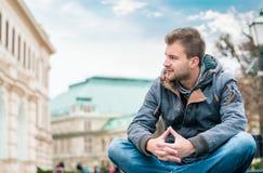 Junger Mann, der zur Seite und zum Sitzen schaut Kerl, der warm tragen oder Winterjacke Lizenzfreies Stockfoto