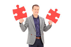 Junger Mann, der zwei Stücke des Puzzlespiels hält Stockfoto