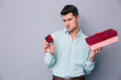 Junger Mann, der zwischen kleiner und großer Geschenkbox wählt Stockfotos