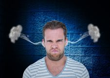 junger Mann des Ärgers mit Dampf auf Ohren Schwarzer und blauer Hintergrund Lizenzfreies Stockfoto