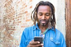 Junger Mann des Afroamerikanerhippies, der intelligentes Mobiltelefon verwendet Stockbild