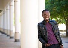 Junger Mann des Afroamerikaners, der in der schwarzen Lederjacke lächelt Stockbild