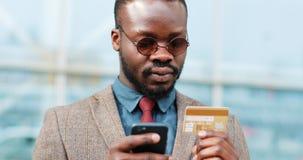 Junger Mann des Afroamerikaners in der Sonnenbrille online kaufend mit Kreditkarte unter Verwendung des intelligenten Telefons in stock video