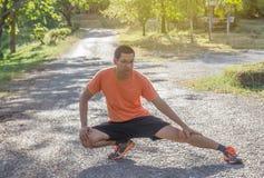 Junger Mann des attraktiven Sitzes, der vor Übung im Park ausdehnt stockbild