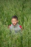 Junger Mann des glücklichen Jungen auf einem grünen Kornfeld Lizenzfreie Stockbilder
