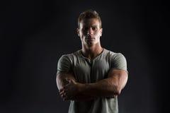 Junger Mann des hübschen muskulösen Sitzes auf dunklem Hintergrund mit strengem Ausdruck Lizenzfreies Stockfoto