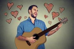 Junger Mann des hübschen Musikers in der Liebe, die Gitarre spielt und ein Lied singt Stockfoto