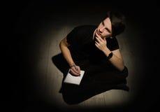 Junger Mann des Jugendlichen, der auf Notizbuch auf schwarzem BAC denkt und schreibt lizenzfreie stockfotos