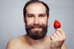 Junger Mann des Nahaufnahmeporträts, der eine Erdbeere und ein Lächeln hält Lizenzfreies Stockbild