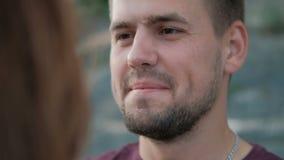 Junger Mann des Porträts betrachtet Frau und küsst sie und draußen steht auf Strand stock video footage