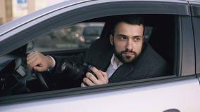 Junger Mann des privaten Detektivs, der innerhalb des Autos sitzt und mit dslr Kamera fotografiert Stockbilder