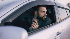 Junger Mann des privaten Detektivs, der innerhalb des Autos sitzt und mit dslr Kamera fotografiert Lizenzfreie Stockbilder