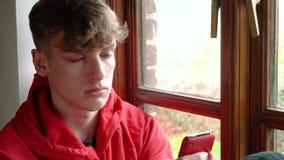 Junger Mann des traurigen deprimierten jugendlich männlichen Jugendlichen, der aus einem Fenster heraus schaut und Mobilhandy für stock video footage