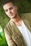 Junger Mann draußen gegen einen Baum Stockfotos