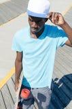 Junger Mann draußen mit Skateboard stockbilder