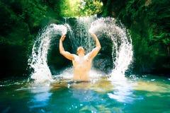 Junger Mann durch den Wasserfall Lizenzfreie Stockbilder