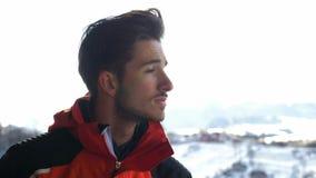 Junger Mann durchnässt von einer Schale heißem Kaffee auf einer hölzernen Plattform im Winter und im Bewundern der Landschaft stock video footage