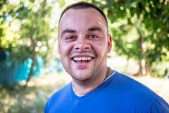 Junger Mann in einem blauen T-Shirt mit einem abgebrochenen Zahn lizenzfreie stockfotografie