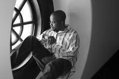 Junger Mann in einem Fenster Lizenzfreies Stockbild