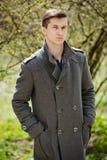 Junger Mann in einem grauen Mantel stockfoto