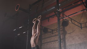 Junger Mann in einem in guter Verfassung, das MuskelUPS tut, trainiert auf den Sportringen an der Turnhalle
