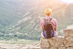 Junger Mann in einem Hut mit einem Rucksack sitzt auf einer Steinwand gegen einen Hintergrund von grünen Bergen Rückseitige Ansic Stockbilder