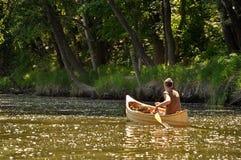 Junger Mann in einem Kanu Stockbild