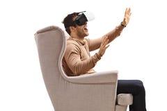 Junger Mann in einem Lehnsessel watchin auf einem Kopfhörer der virtuellen Realität stockfotografie