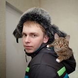 Junger Mann in einem Pelzhut mit einem Kätzchen der getigerten Katze Farbin der Haube seiner Jacke lizenzfreies stockfoto