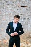 junger Mann in einem schwarzen Anzug auf einem Hintergrund einer Backsteinmauer Stockbild
