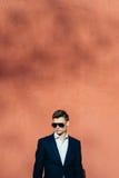 junger Mann in einem schwarzen Anzug auf einem Hintergrund einer Backsteinmauer Lizenzfreie Stockfotos