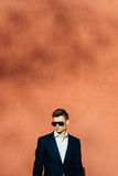 junger Mann in einem schwarzen Anzug auf einem Hintergrund einer Orange wal Stockbild