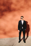 junger Mann in einem schwarzen Anzug auf einem Hintergrund einer orange Wand Lizenzfreie Stockfotografie