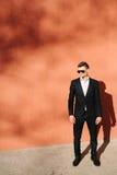 junger Mann in einem schwarzen Anzug auf einem Hintergrund einer orange Wand Stockbilder
