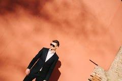junger Mann in einem schwarzen Anzug auf einem Hintergrund einer orange Wand Lizenzfreies Stockfoto