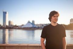 Junger Mann in einem schwarzen T-Shirt auf den Banken des Flusses, Stadtbild, ruhiges Gesicht Weicher Fokus tonen Stockfoto