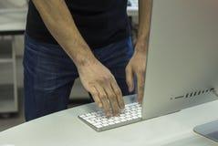 Junger Mann in einem schwarzen T-Shirt, das mit dem Computer, stehend arbeitet Stockfoto