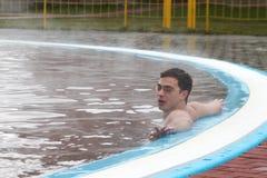 Junger Mann in einem thermischen Pool Stockbild