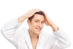 Junger Mann in einem weißen Bademantel, der sein Haar herstellt Stockfoto