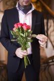 Junger Mann in einer Klage mit Rosen in ihren Händen Stockfotografie