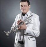 Junger Mann in einer weißen Klage mit einer Trompete Getrennt auf schwarzem Hintergrund stockbild