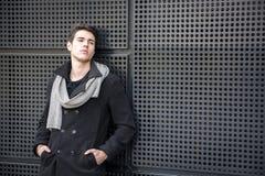 Junger Mann in einer Winter-Ausstattung, die auf Metallwand, großes Copyspace sich lehnt Stockfotos