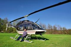 Junger Mann entspannt sich nahe bei kleinem Hubschrauber Lizenzfreies Stockfoto