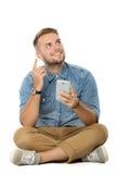 Junger Mann erhalten eine Inspiration beim Halten eines Mobiltelefons und des sitti Lizenzfreie Stockfotografie